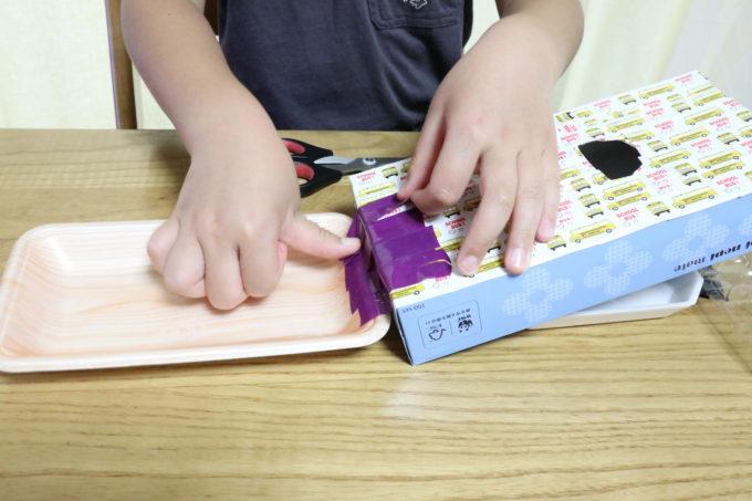 完成品の形に、準備するものにある容器JKLを置いて、ビニールテープで貼り付けます。